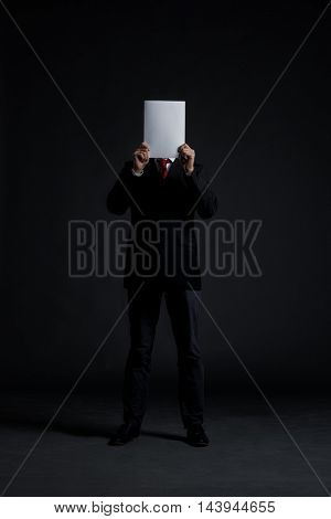 Businessman with a blank paper over his face. Black background. Business and office concept.