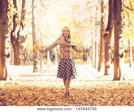 Young and attractive girl walking in autumn park with a bouquet of fallen maple leaves.