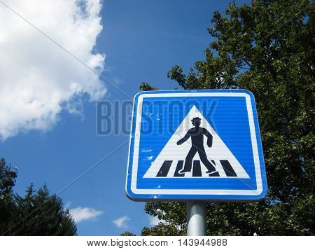 Pedestrian walk sign on a natural sky clouds and trees summer background