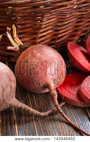 Beetroots on wooden table with old woven basket in background