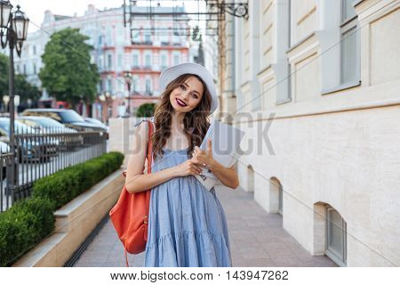 Cheerful cute young woman with red backpack standing on the street and holding blank magazines
