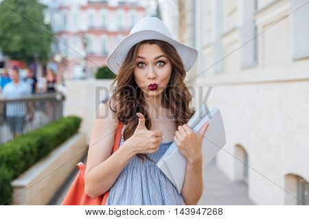 Funny pretty young woman in hat with blank magazines showing thumbs up on the street