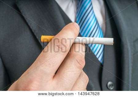Man (smoker) holds tobacco cigarette in hand.