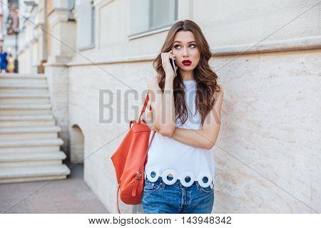 Pretty sad upset young woman talkingon the phone outdoors