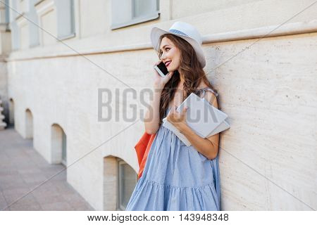 Smiling woman with blank covered books standing on the street and talking on cell phone