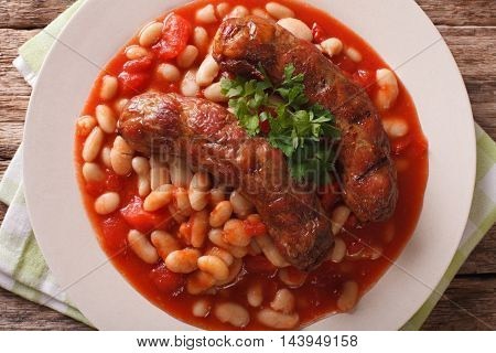 Pork Sausages With Beans And Cooked Tomatoes On A Plate Closeup. Horizontal Top View