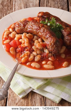 Grilled Sausage With Beans In Tomato Sauce On A Plate Close-up. Vertical
