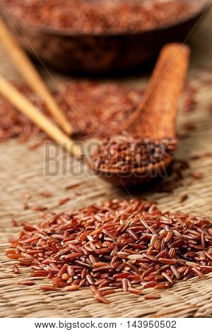 red rice wooden spoon chopsticks on a straw background