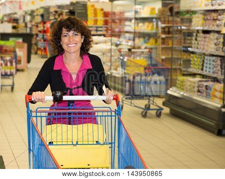 Brunette Woman Driving Shopping Cart While Grocery Shopping In Supermarket