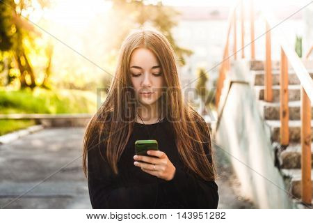 A young girl is using the phone. Student listening to music on headphones.