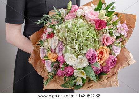 Vintage floristic background, colorful roses, antique scissors and a rope on an wooden table