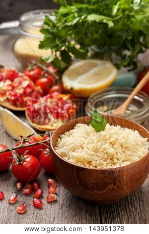 cooked couscous fresh vegetables for salad: tomatoes pomegranate lemon parsley and olive oil on a wooden background
