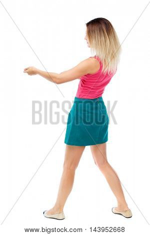 back view of standing girl pulling a rope from the top or cling to something. girl  watching. Rear view people collection.  backside view of person.  Isolated over white background. Blonde in a red