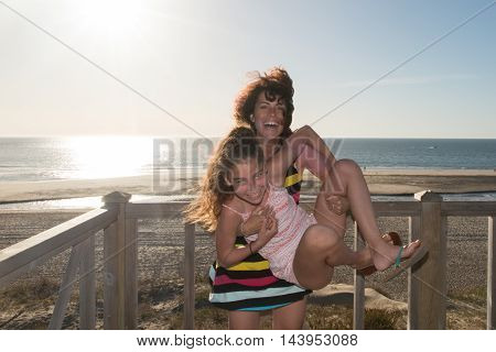 Mother And Daughter Playing Togeather At Beach Smiling