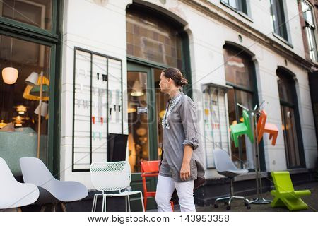Young brunette woman passing a furniture shop