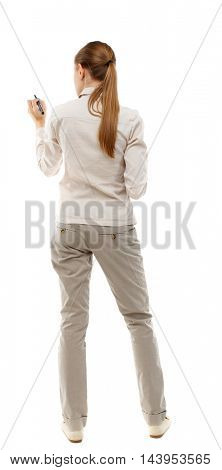 back view of writing beautiful woman. Rear view people collection.  backside view of person. Isolated over white background. Skinny girl in white denim suit writes a pen.
