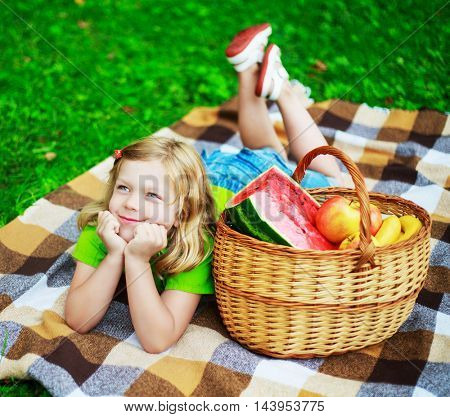 happy child with a fruit basket having a picnic outdoor on a summer day