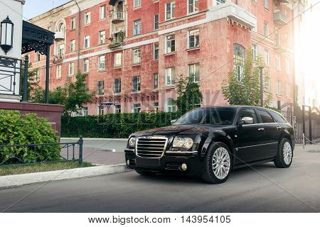 Saratov, Russia - August 9, 2015: Black Car Chrysler 300C Standing On Asphalt Road In The City At Da