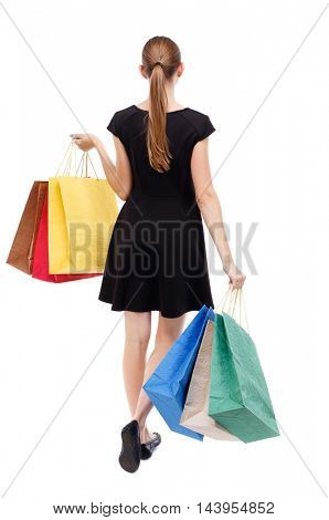 back view of going  woman  with shopping bags . beautiful girl in motion.  backside view of person.  Rear view people collection. Isolated over white background. Blonde in a short black dress resting