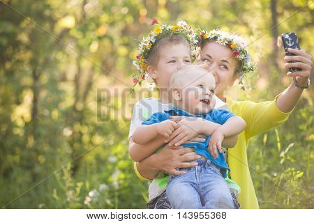 Portrait of adorable kids with their young mother taking selfie in the sunny park. Happy family in flower wreaths making photo with smartphone outdoors on a summer day. Boys and mom smiling.