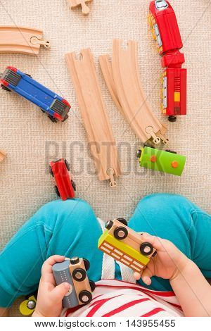 Close-up of toddler's hands playing with railroad and colorful trains. Indoors. Early learning and development. Education. Transport.