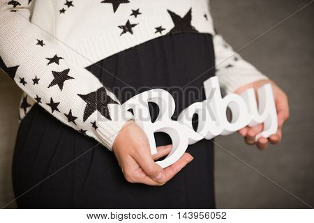 Pregnant woman with Baby sign. Horizontal close-up of a pregnant belly with sign baby.Black background