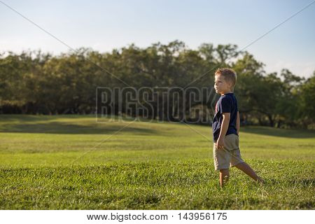 A cute kid boy standing alone in a large grassy meadow. Handsome child in the park looking into the distance. Boy playing on the grass. Weekend in the park. Leisure acitvities. Outdoor. Room for copy.