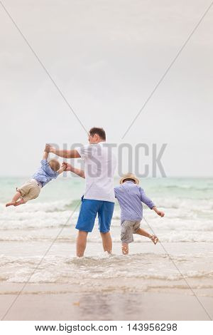 Portrait of father with two sons walking on the ocean beach. Summer vacations by the sea. Outdoors. Happy family.