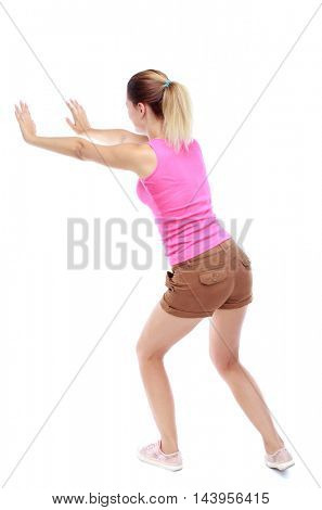 back view of woman pushes wall.  Isolated over white background. Rear view people collection. backside view of person. Sport blond in brown shorts pushing something on the side.