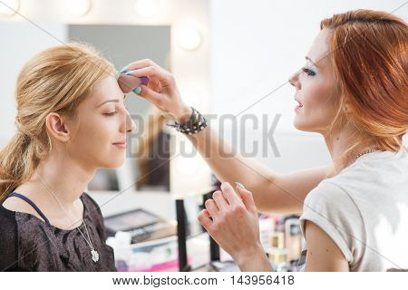 Make-up artist applying colors to model