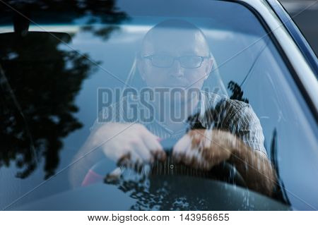 Portrait of young happy businessman with glasses in the car