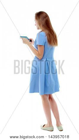 back view of standing young beautiful  woman using a mobile phone or tablet computer. girl  watching. Rear view people collection.  backside view of person.  Isolated over white background. Skinny