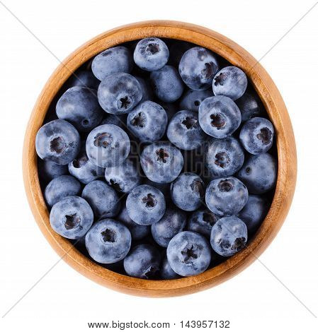 Blueberries in a wooden bowl on white background. Dark purple colored ripe berries of Vaccinium corymbosum. Edible fruits, raw, organic and vegan food. Isolated macro photo close up from above.