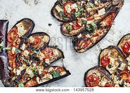Top view shot of baked sliced eggplants in fan shape with cheese feta, tomatoes, basil leaves, crumbled walnut, olive oil. Unusual garnish dish on metal background. Vegetarian cuisine just from oven