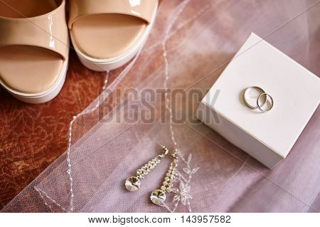 Wedding rings and earrings on a white veil of bride.