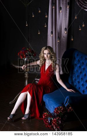 Beautiful young blonde woman in red dress with halloween make up and bloody face art vintage interior