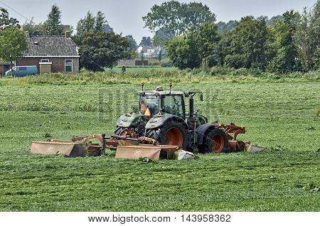 YSBRECHTUM, THE NETHERLANDS - AUGUST 24, 2016: A Fendt 720 tractor with with a Lely Splendimo Triplo 900 MC mower, equipped with condition fingers, cutting 8.9 m grass at once, as seen from behind.