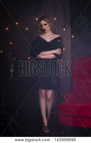 Beautiful young blonde woman in black dress with halloween make up and bloody face art vintage interior