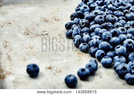 Close up shot of big pile of natural, freshly picked blueberries. Organic, eco friendly food for healthy lifestyle. A lot of berries on metal background. Place for text, soft edge, bright deep colors