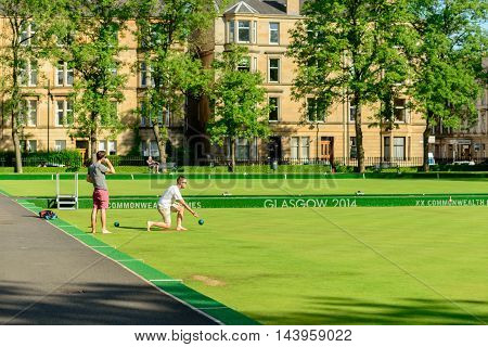 GLASGOW SCOTLAND - JULY 21 2016: Two men playing barefoot bowls at the Kelvin Grove Bowling and Tennis Centre in summer.