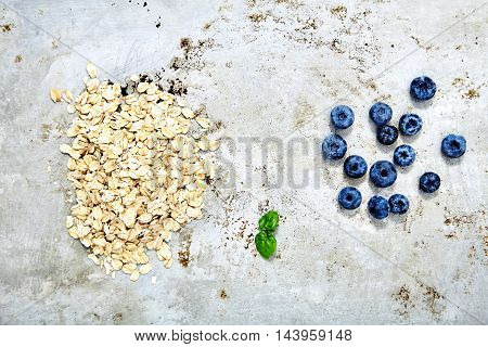 Top view shot of two small piles of fresh blueberries and raw oat flakes with mint leaf between it. Dietary, tasty ingredients for quick, delicious and healthy breakfast. Vitamin, simple food on metal