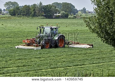 YSBRECHTUM, THE NETHERLANDS - AUGUST 24, 2016: A new Fendt 720 tractor with a Lely Splendimo Triplo 900 MC mower, equipped with condition fingers, cutting 8.9 m grass at once, as seen at front.