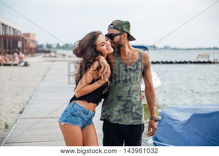 Happy young couple in love kissing at the wooden sea pier