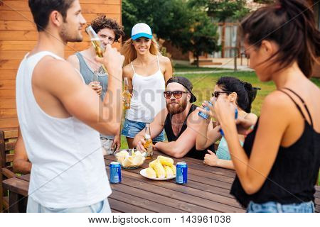 Group of happy young friends eating and drinking beer outdoors