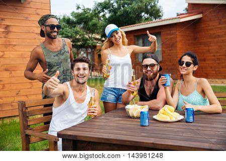 Group of cheerful young people drinking beer and showing thumbs up at the table outdoors