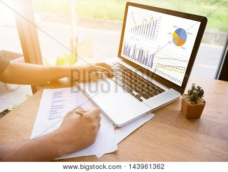 Accountants work analyzing financial reports on a laptop in a cafe.