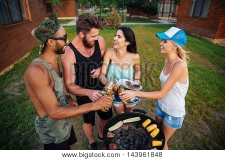 Multiethnic group of young people cooking food on barbeque and celebrating outdoors