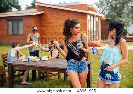 Two beautiful young women talking and drining soda with friends on summer outdoor party