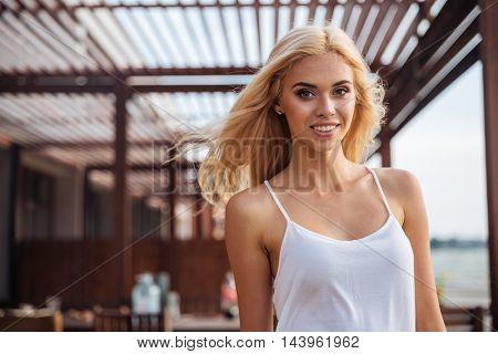 Happy cute young woman with blonde hair standing outdoors on the wind