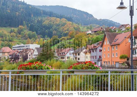 Autumn city landscape with hills and blossoming geranium on Murg river bridge in Gernsbach, Germany